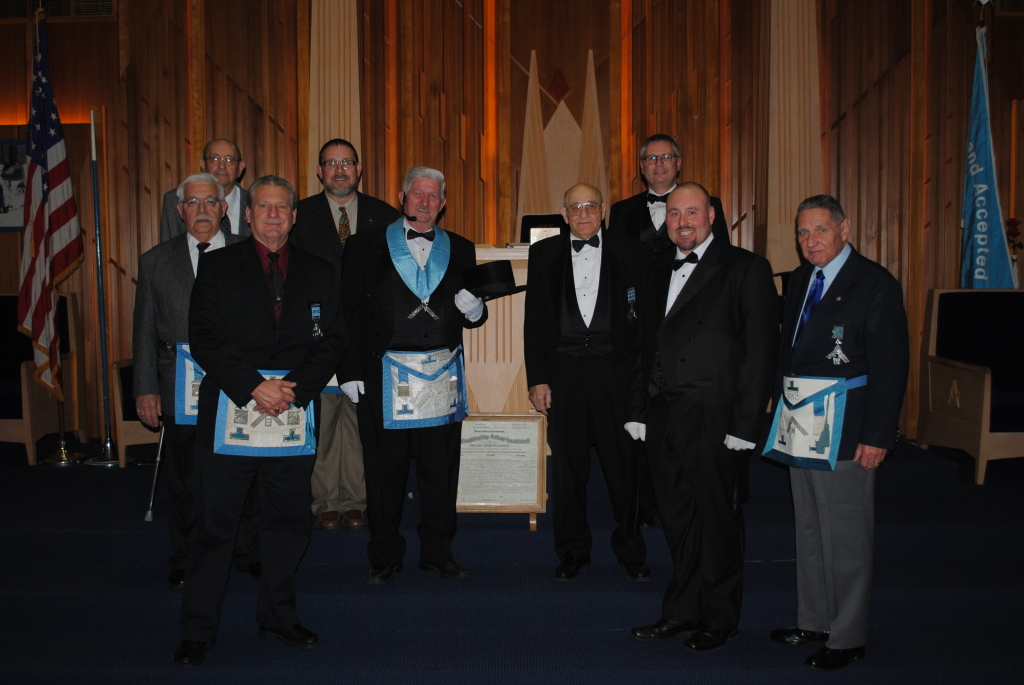 The Past Master of Abraham C. Treichler Lodge No. 682 congratulate Bro. H. Eugene Geib (Center, in regalia) on being installed as the 100th Worshipful Master of the Lodge.